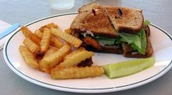 A soft shell crab sandwich with french fries and a pickle