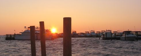 A photo of the sun rising over boats
