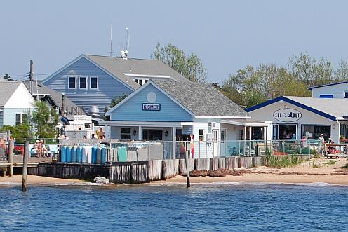 A small pier and sandy beach with several attractive buildings