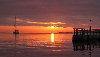 A sailboat, sunset, and pier
