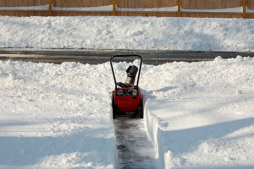 A small snowblower cutting through deep snow