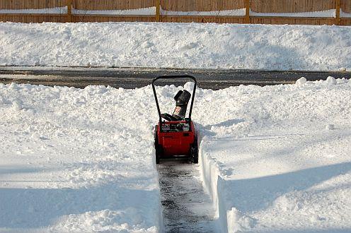 A small snowblower cutting through deep snow
